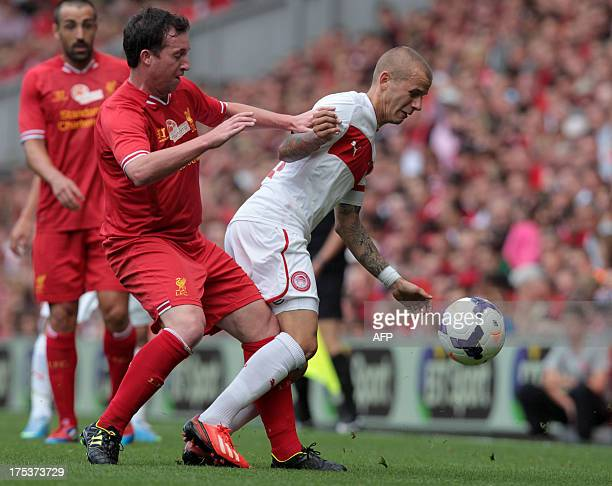 Liverpool's former player Robbie Fowler vies with Olympiakos's Slovakian midfielder Vladimir Weiss during the preseason friendly football match...