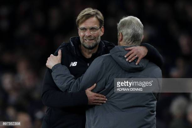 Liverpool's German manager Jurgen Klopp and Arsenal's French manager Arsene Wenger embrace after the English Premier League football match between...