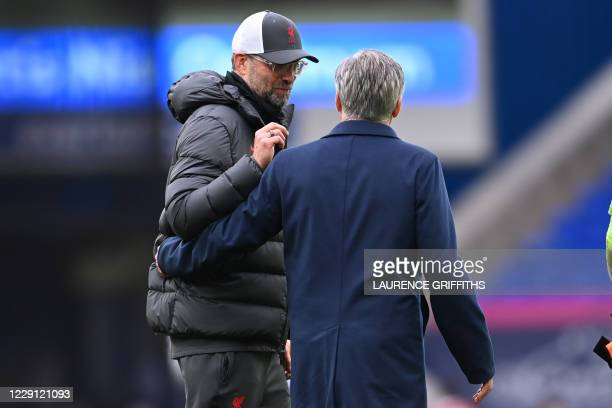 Liverpool's German manager Jurgen Klopp and Everton's Italian head coach Carlo Ancelotti react at the final whistle during the English Premier League...