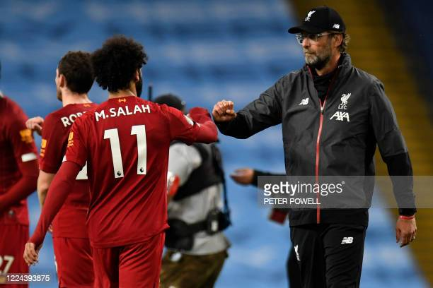 Liverpool's German manager Jurgen Klopp and Liverpool's Egyptian midfielder Mohamed Salah on the pitch after the English Premier League football...