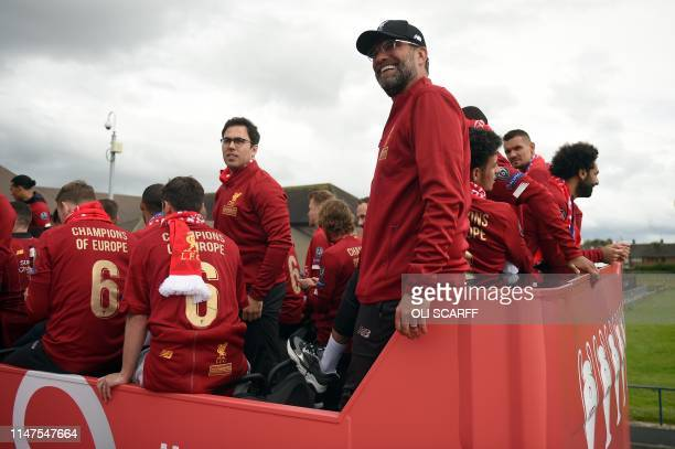 Liverpool's German manager Jurgen Klopp and Liverpool's Egyptian midfielder Mohamed Salah stand atop an opentop bus ahead of a parade around...
