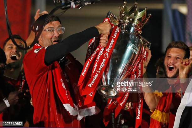 Liverpool's German manager Jurgen Klopp and Liverpool's English midfielder Adam Lallana pose with the Premier League trophy during the presentation...