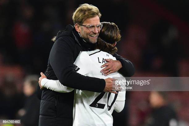 Liverpool's German manager Jurgen Klopp and Liverpool's English midfielder Adam Lallana embrace on the pitch after the English Premier League...