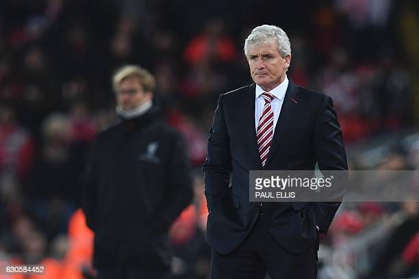 Liverpool's German manager Jurgen Klopp and Stoke City's Welsh manager Mark Hughes stand on the touchline during the English Premier League football...