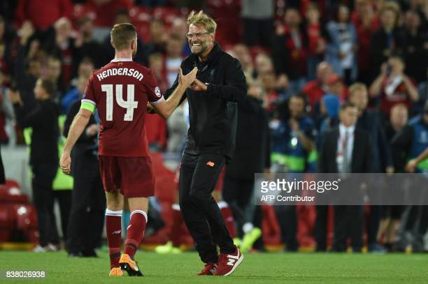 TOPSHOT Liverpool's German manager Jurgen Klopp celebrates victory with Liverpool's English captain Jordan Henderson after the Champions League...
