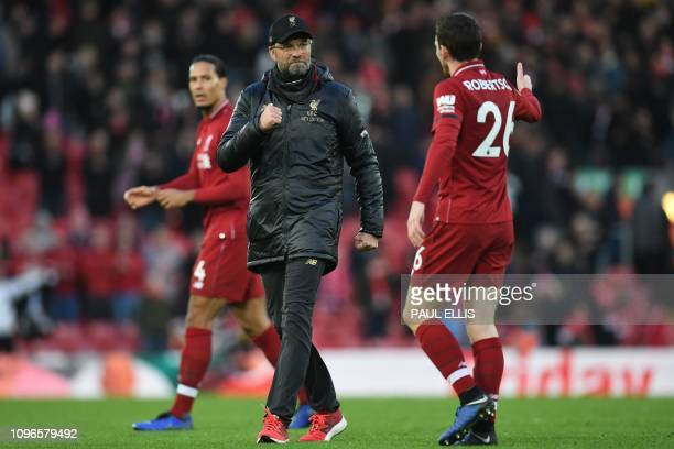 Liverpool's German manager Jurgen Klopp celebrates with Liverpool's Scottish defender Andrew Robertson on the pitch after the English Premier League...