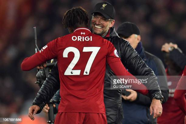 Liverpool's German manager Jurgen Klopp embraces Liverpool's Belgian striker Divock Origi on the pitch after the English Premier League football...