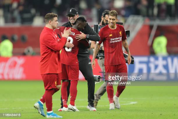 Liverpool's German manager Jurgen Klopp embraces Liverpool's Guinean midfielder Naby Keita following the 2019 FIFA Club World Cup semifinal football...