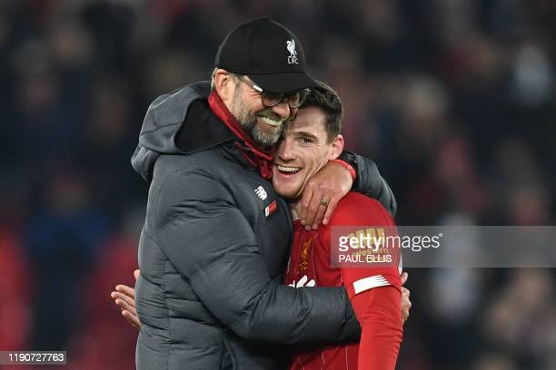 Liverpool's German manager Jurgen Klopp embraces Liverpool's Scottish defender Andrew Robertson at the end of the English Premier League football...
