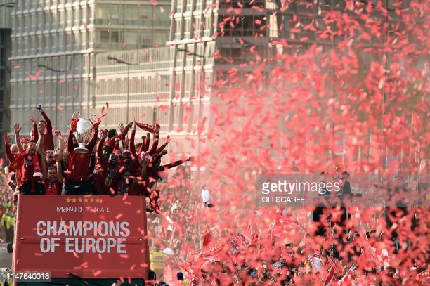 TOPSHOT Liverpool's German manager Jurgen Klopp holds the European Champion Clubs' Cup trophy as he stands with his players during an opentop bus...