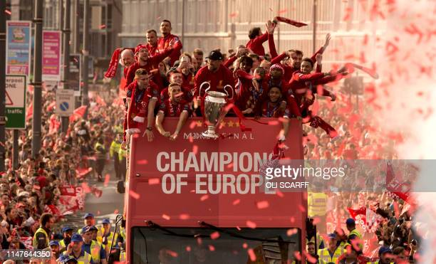Liverpool's German manager Jurgen Klopp holds the European Champion Clubs' Cup trophy as he stands with his players during an opentop bus parade...