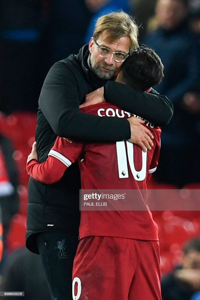 Liverpool's German manager Jurgen Klopp (L) hugs Liverpool's Brazilian midfielder Philippe Coutinho (R) applauds after the final whistle during the English Premier League football match between Liverpool and Swansea City at Anfield in Liverpool, north west England on December 26, 2017. / AFP PHOTO / Paul ELLIS / RESTRICTED TO EDITORIAL USE. No use with unauthorized audio, video, data, fixture lists, club/league logos or 'live' services. Online in-match use limited to 75 images, no video emulation. No use in betting, games or single club/league/player publications. /