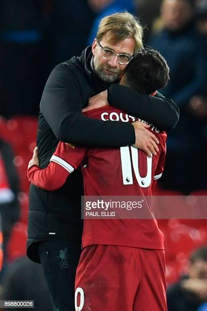 Liverpool's German manager Jurgen Klopp hugs Liverpool's Brazilian midfielder Philippe Coutinho applauds after the final whistle during the English...
