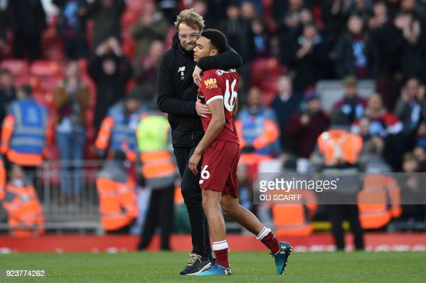 Liverpool's German manager Jurgen Klopp hugs Liverpool's English midfielder Trent AlexanderArnold at the final whistle of the English Premier League...