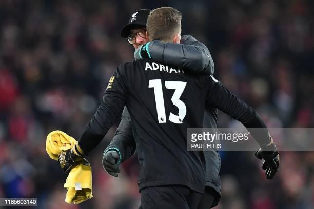 Liverpool's German manager Jurgen Klopp hugs Liverpool's Spanish goalkeeper Adrian following the English Premier League football match between...