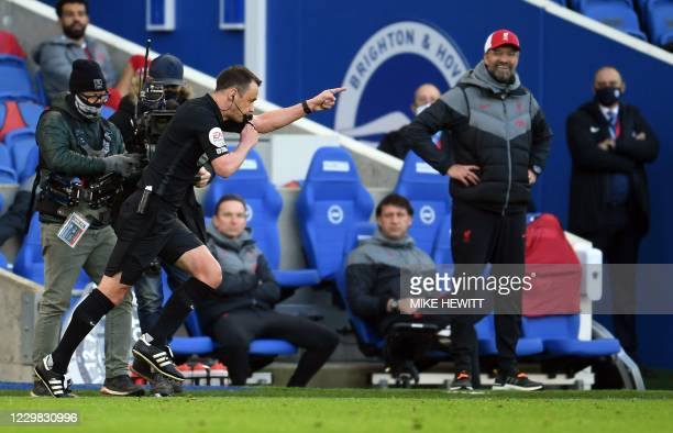 Liverpool's German manager Jurgen Klopp looks on as referee Stuart Attwell awards a penalty after consulting VAR during the English Premier League...