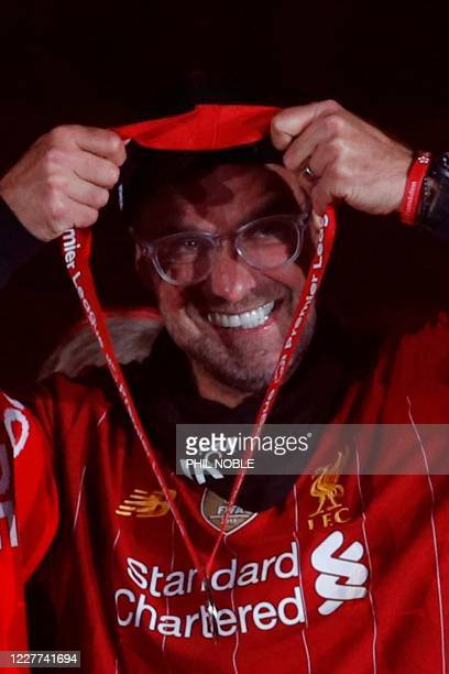 Liverpool's German manager Jurgen Klopp recieves his medal next to the Premier League trophy during the presentation following the English Premier...