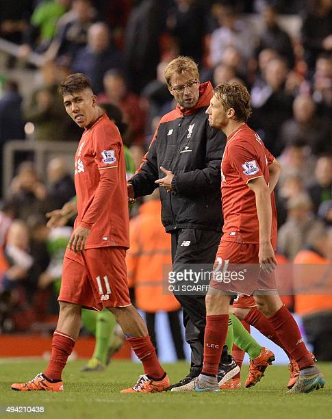 Liverpool's German manager Jurgen Klopp speaks to Liverpool's Brazilian midfielder Lucas Leiva as he leaves the pitch after the English Premier...