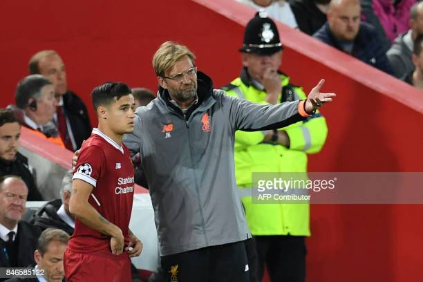 Liverpool's German manager Jurgen Klopp speaks to Liverpool's Brazilian midfielder Philippe Coutinho as he prepares to play during the UEFA Champions...