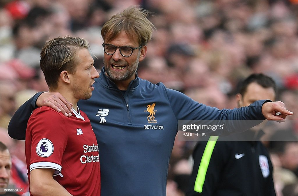 Liverpool's German manager Jurgen Klopp (R) talks to Liverpool's Brazilian midfielder Lucas Leiva as he waits to be substituted on during the English Premier League football match between Liverpool and Middlesbrough at Anfield in Liverpool, north west England on May 21, 2017. / AFP PHOTO / Paul ELLIS / RESTRICTED TO EDITORIAL USE. No use with unauthorized audio, video, data, fixture lists, club/league logos or 'live' services. Online in-match use limited to 75 images, no video emulation. No use in betting, games or single club/league/player publications. /