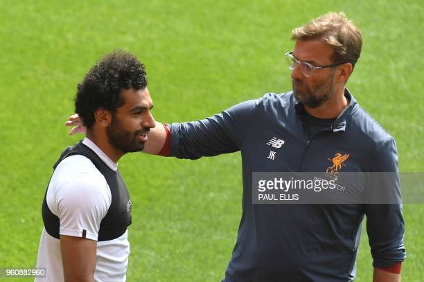 Liverpool's German manager Jurgen Klopp talks with Liverpool's Egyptian midfielder Mohamed Salah as he attends a training session and media day at...