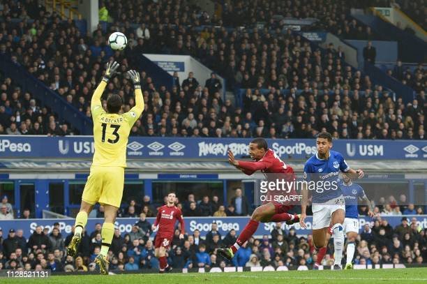 Liverpool's Germanborn Cameroonian defender Joel Matip blocks Everton's English striker Dominic CalvertLewin during the English Premier League...