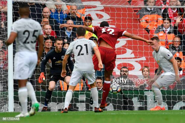 Liverpool's Germanborn Cameroonian defender Joel Matip shoots from close range forcing a save from Manchester United's Spanish goalkeeper David de...