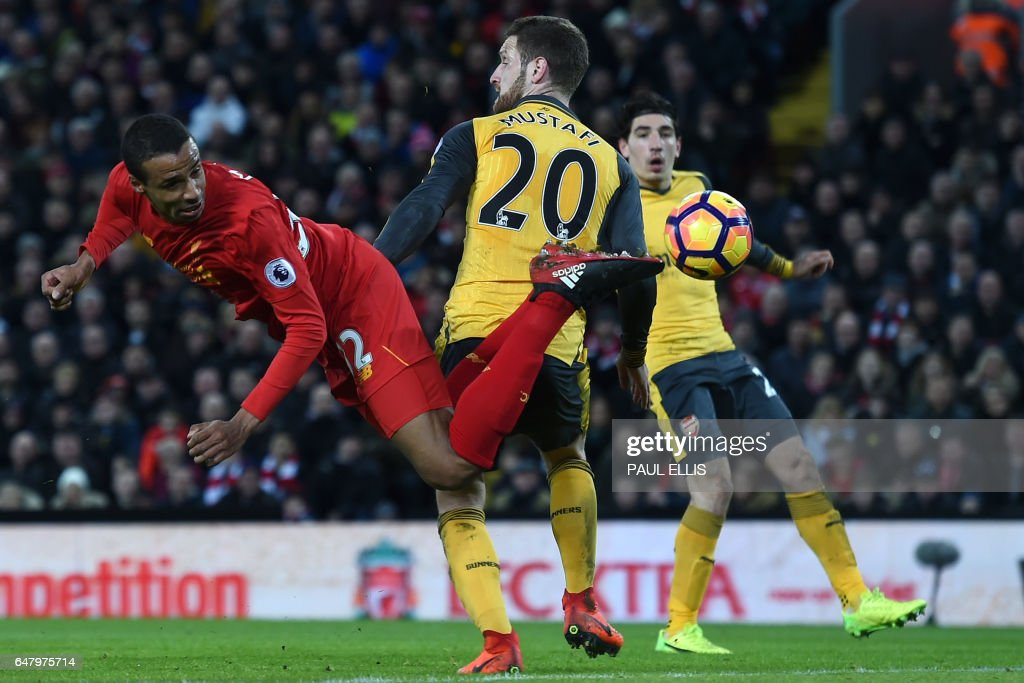 TOPSHOT - Liverpool's German-born Cameroonian defender Joel Matip (L) tries to reach the ball during the English Premier League football match between Liverpool and Arsenal at Anfield in Liverpool, north west England on March 4, 2017. Liverpool won the game 3-1. / AFP PHOTO / Paul ELLIS / RESTRICTED TO EDITORIAL USE. No use with unauthorized audio, video, data, fixture lists, club/league logos or 'live' services. Online in-match use limited to 75 images, no video emulation. No use in betting, games or single club/league/player publications. /