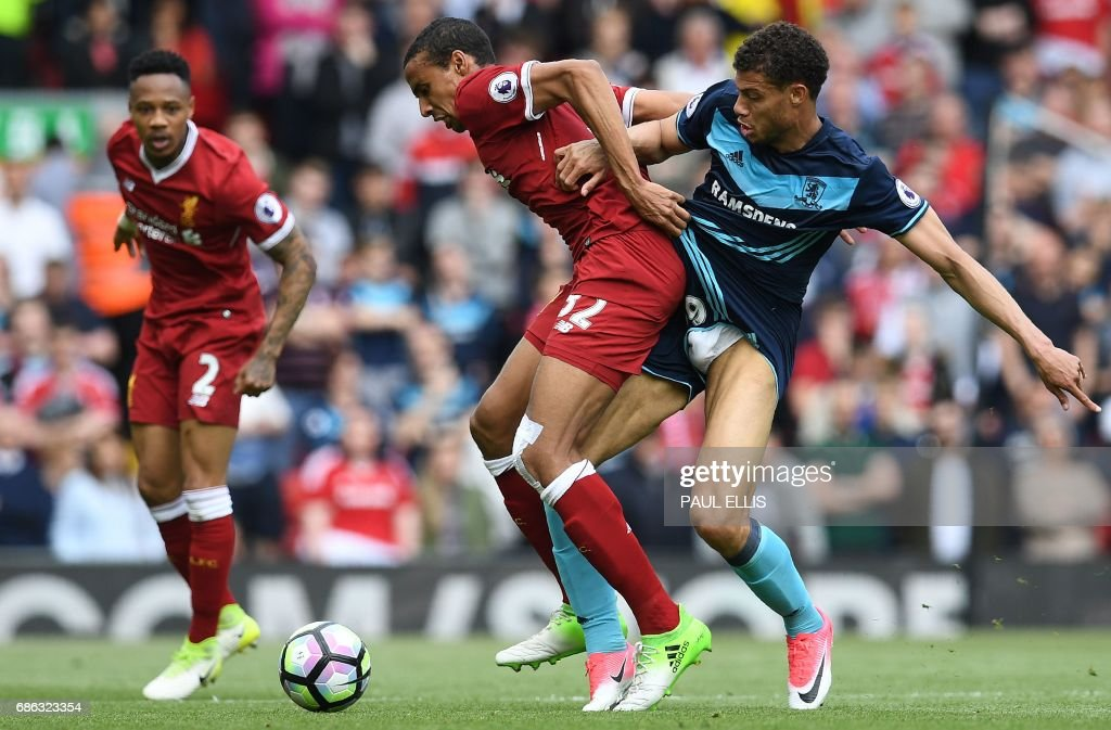 Liverpool's German-born Cameroonian defender Joel Matip (C) vies with Middlesbrough's French striker Rudy Gestede during the English Premier League football match between Liverpool and Middlesbrough at Anfield in Liverpool, north west England on May 21, 2017. / AFP PHOTO / Paul ELLIS / RESTRICTED TO EDITORIAL USE. No use with unauthorized audio, video, data, fixture lists, club/league logos or 'live' services. Online in-match use limited to 75 images, no video emulation. No use in betting, games or single club/league/player publications. /