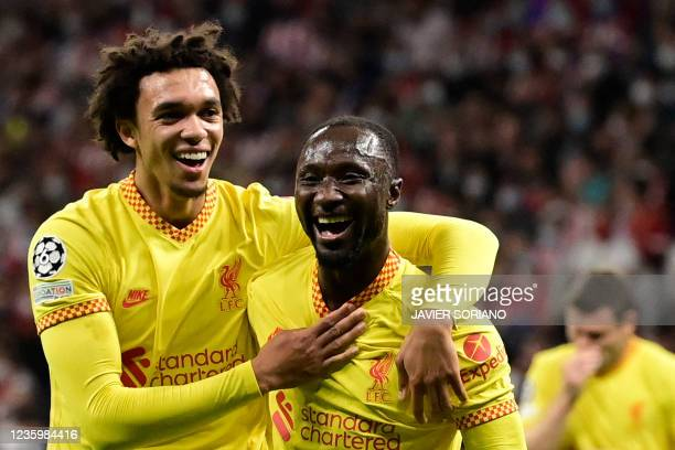 Liverpool's Guinean midfielder Naby Keita celebrates with teammate Liverpool's English defender Trent Alexander-Arnold after scoring a goal during...