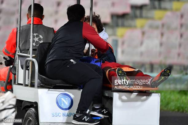 Liverpool's Guinean midfielder Naby Keita is being driven away into a cart after being injured during the UEFA Champions League group C football...