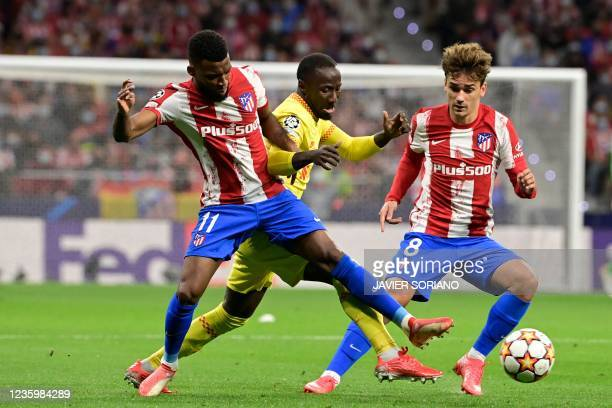 Liverpool's Guinean midfielder Naby Keita vies with Atletico Madrid's French midfielder Thomas Lemar and Atletico Madrid's French forward Antoine...