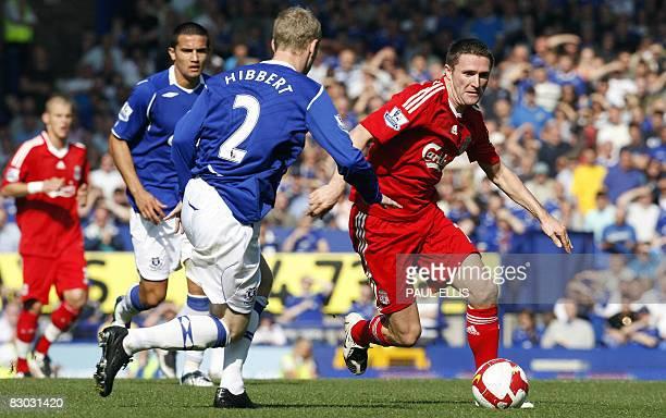 Liverpool's Irish forward Robbie Keane runs towards Everton's English defender Tony Hibbert during their English Premier League football match at...