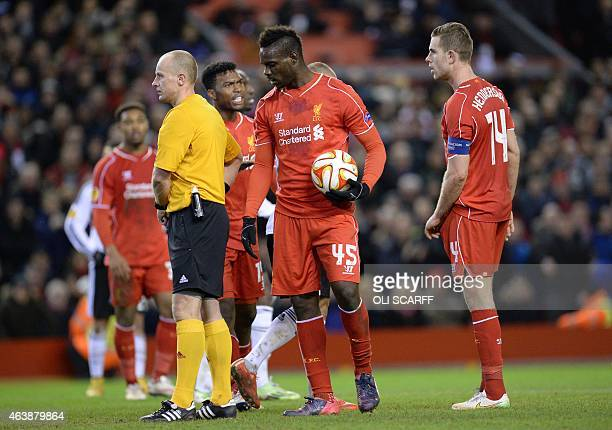 Liverpool's Italian striker Mario Balotelli holds the ball before placing it on the penalty spot to take the kick and score after taking it from...