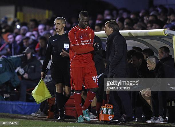 Liverpool's Italian striker Mario Balotelli speaks to Liverpool's Northern Irish manager Brendan Rodgers before coming on as substitute during the...