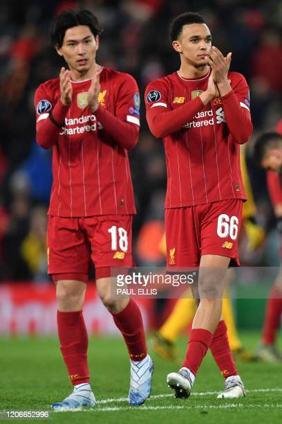 Liverpool's Japanese midfielder Takumi Minamino and Liverpool's English defender Trent AlexanderArnold react at the final whistle during the UEFA...