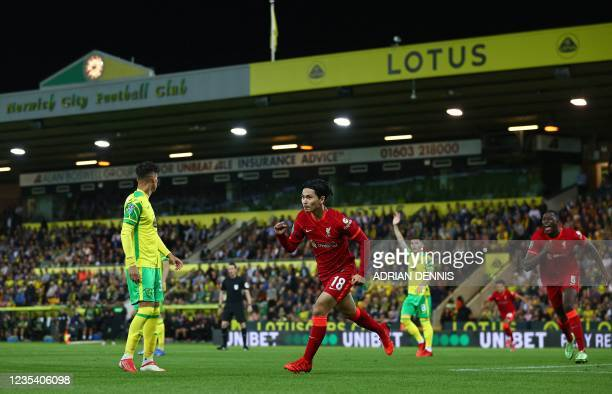 Liverpool's Japanese midfielder Takumi Minamino celebrates scoring the opening goal during the English League Cup third round football match between...