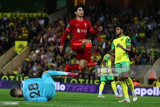 Liverpool's Japanese midfielder Takumi Minamino jumps Norwich City's English goalkeeper Angus Gunn during the English League Cup third round football...