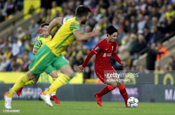 Liverpool's Japanese midfielder Takumi Minamino runs with the ball during the English League Cup third round football match between Norwich City and...