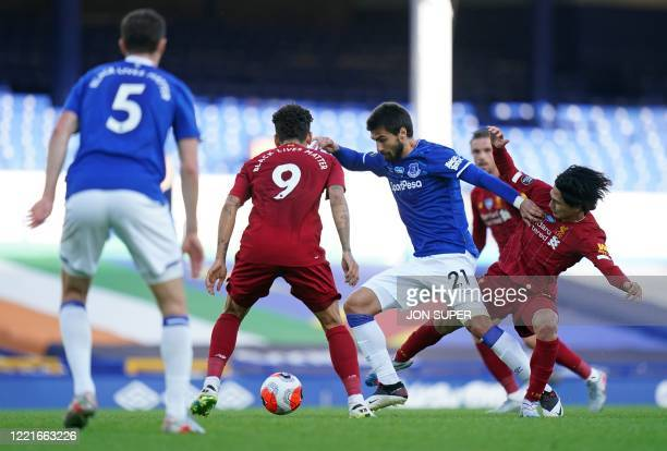Liverpool's Japanese midfielder Takumi Minamino tackles Everton's Portuguese midfielder André Gomes during the English Premier League football match...