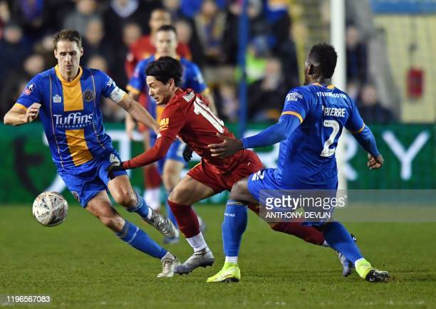 Liverpool's Japanese midfielder Takumi Minamino vies for the ball against Shrewsbury Town's Grenadian defender Aaron Pierre and Shrewsbury Town's...