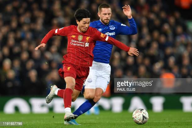 Liverpool's Japanese midfielder Takumi Minamino vies with Everton's Icelandic midfielder Gylfi Sigurdsson during the English FA Cup third round...