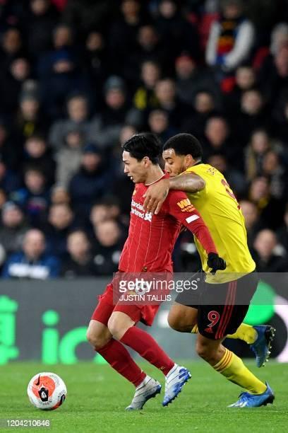 Liverpool's Japanese midfielder Takumi Minamino vies with Watford's English striker Troy Deeney during the English Premier League football match...