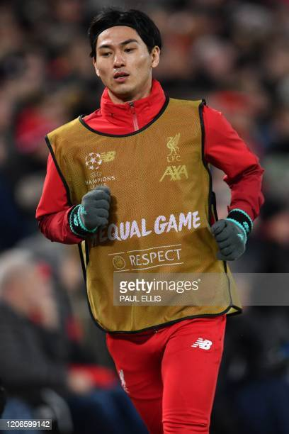 Liverpool's Japanese midfielder Takumi Minamino warms up during the UEFA Champions league Round of 16 second leg football match between Liverpool and...