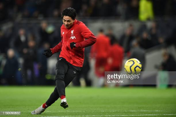 Liverpool's Japanese midfielder Takumi Minamino warms up for the English Premier League football match between Tottenham Hotspur and Liverpool at...