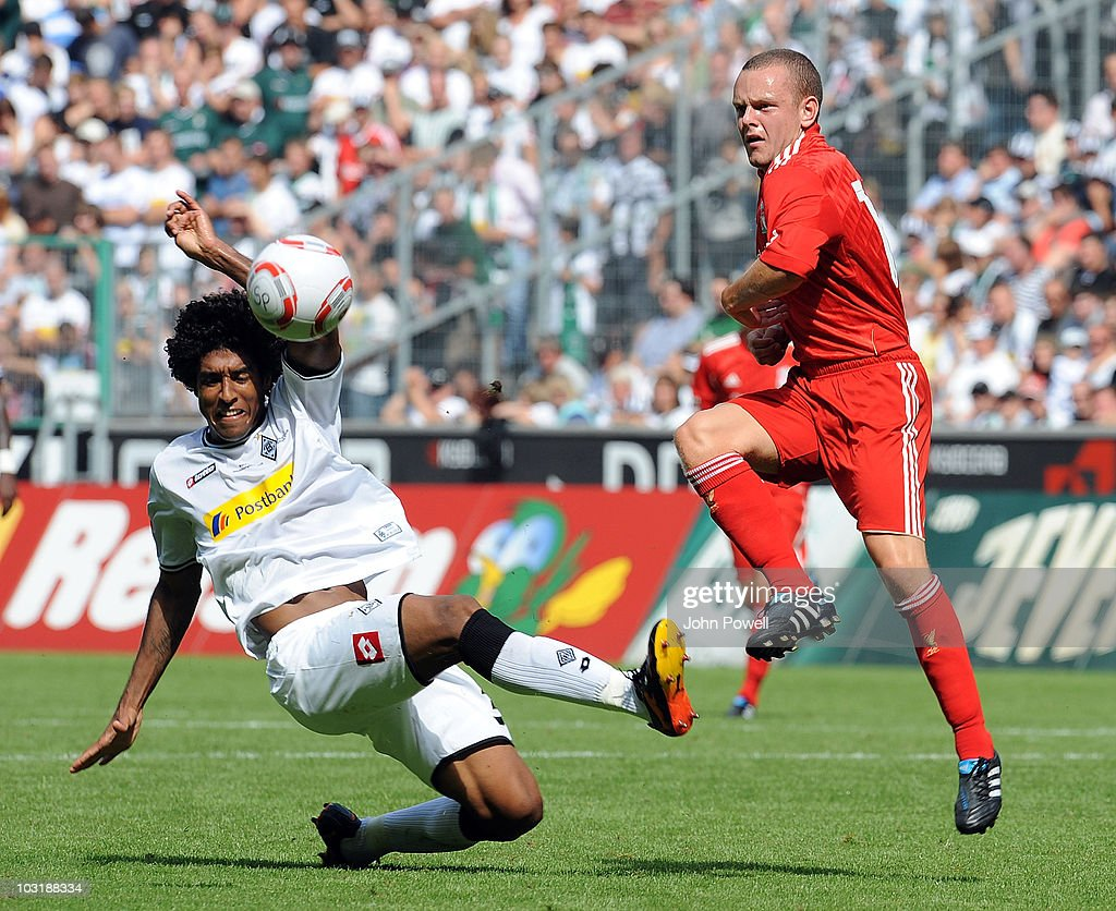 Liverpools Jay Spearing (R) gets to the ball in front of Dante during the pre-season friendly match between Borussia M'Gladbach and Liverpool at the Borussia Park Stadium on August 1, 2010 in Moenchengladbach, Germany.