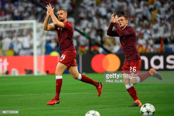Liverpool's Liverpool's English midfielder Jordan Henderson and Liverpool's Scottish defender Andrew Robertson warm up for the UEFA Champions League...