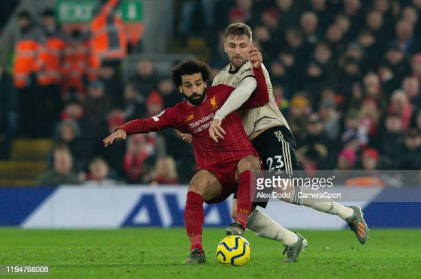 Liverpool's Mohamed Salah battles with Manchester United's Luke Shaw during the Premier League match between Liverpool FC and Manchester United at...