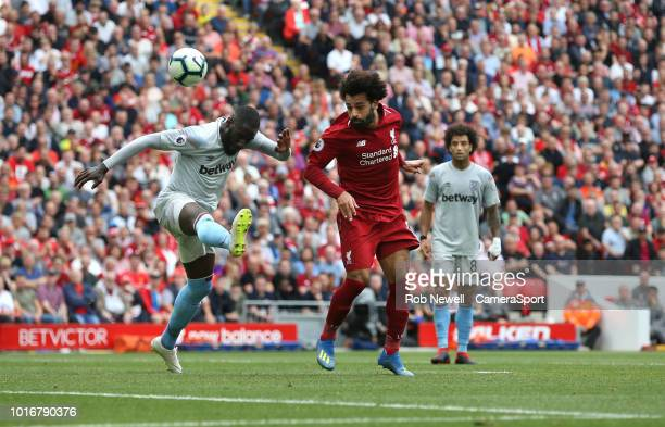 Liverpool's Mohamed Salah gets in a header under pressure from West Ham United's Arthur Masuaku during the Premier League match between Liverpool FC...