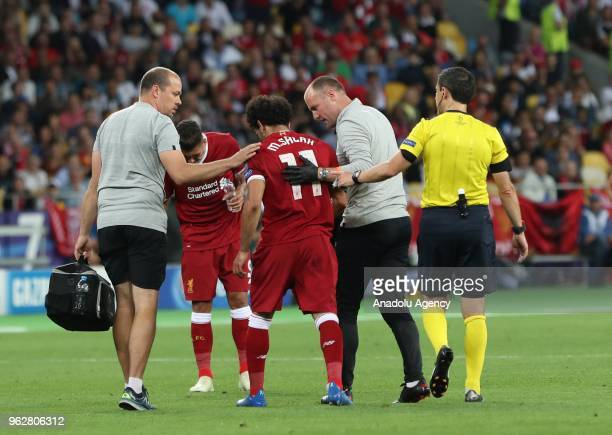 Liverpool's Mohamed Salah leaves the pitch after getting injured during the UEFA Champions League final football match between Real Madrid and...